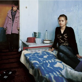 Female trafficked victim sitting on a bed