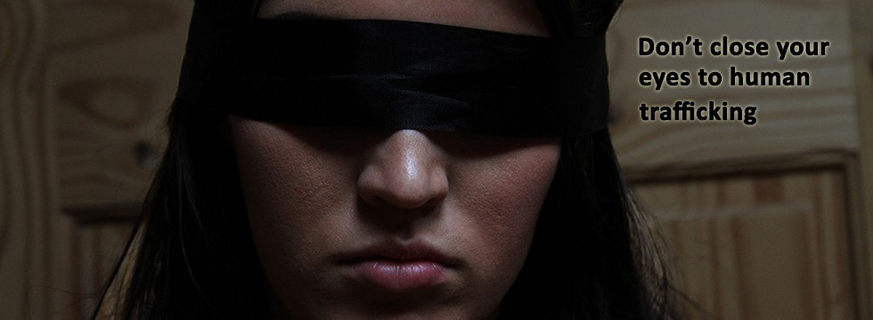 A girl with a blindfold and text saying 'Don't close your eyes to human trafficking'.